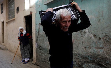 A man carries belongings through a narrow back alley of Sur, a historical district of the southeastern city of Diyarbakir