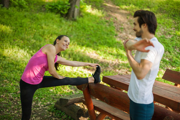 Couple is exercising in park. They are stretching bodies.
