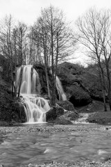 Beautiful Serbian waterfall long time exposure photography, water motion in black and white. Winter image with river in front