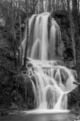 Beautiful Serbian waterfall long time exposure photography, water motion in black and white. Winter close-up image