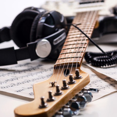 Electric guitar and headphones with music notes.