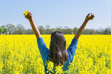 Happy woman arms up in yellow field of flowers