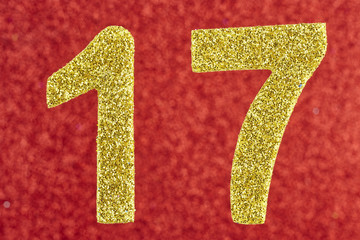 Number seventeen golden color over a red background. Anniversary.