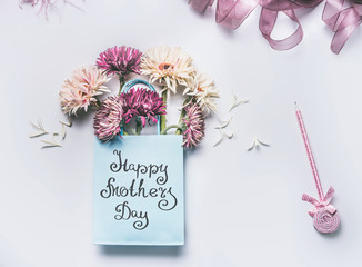 Happy Mothers day! Greeting card with fresh lovely flowers bunch in blue paper shopping bag with pen on white desktop background, Top view , copy space