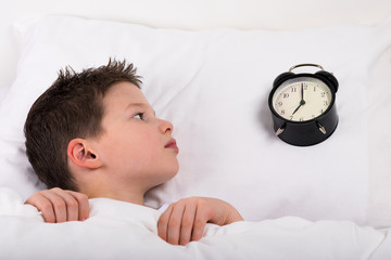 the boy wakes up in bed and looks at the big clock