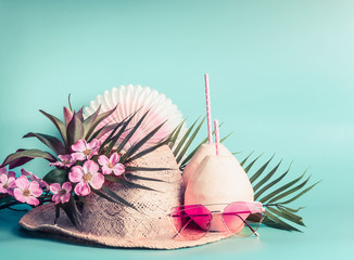 Summer holiday accessories: straw hat, coconut drinks, sunglasses. palm leaves and flowers at turquoise blue background, front view. Tropical and beach vacation concept