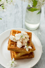 delicious Viennese waffles with ice creamon saucer in spring composition on wooden background