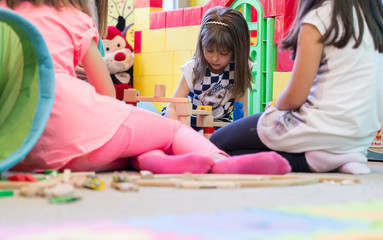 Cute pre-school girl looking down with concentration while building a structure from wooden toy blocks during playtime in a modern kindergarten