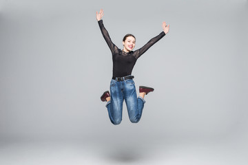 Full length portrait of a cheerful woman jumping isolated on white background