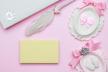 Beautiful pastel pink layout with stone decoration, notepad, bird hair pen, ribbon, hearts on pink background, top view, flat lay, border. Baby shower or Mothers Day greeting concept