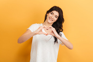 Beautiful young lady showing heart love gesture.