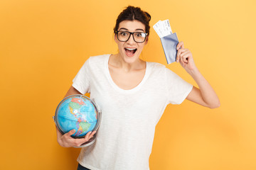 Excited surprised woman wearing glasses holding globe and passport with tickets.