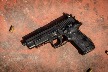 Black 9mm Auto Pistol on the concrete red backgroound
