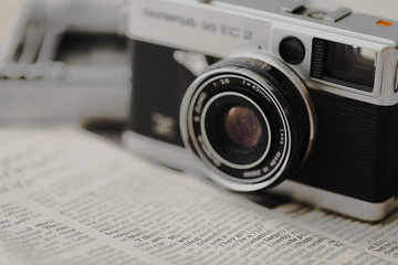 レトロなコンパクトデジタルカメラと英字新聞 Retro compact digital camera and English newspaper