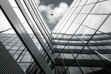 Flying airplane over modern architecture building, low angle black and white high contrast picture  Wall mural
