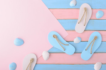 Colored flip flops, seashells and paper for your text on Soft pink and light blue wooden planks background Trendy vanilla pastel colors Top view and copy space Flat lay Summer design