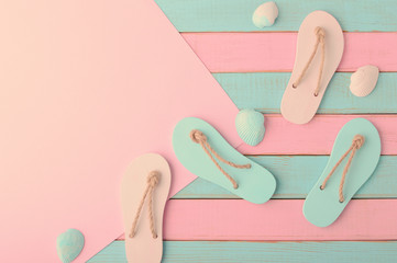 Colored flip flops, seashells and paper for your text on Soft pink and light mint wooden planks background Trendy vanilla pastel colors Top view and copy space Flat lay Summer design
