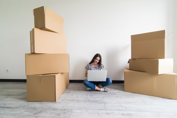 Happy young woman sitting on floor near moving boxes. Young woman moving to new home. Woman using laptop, looking at camera and smiling