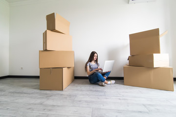 Woman sitting on the floor near a boxes with laptop at home