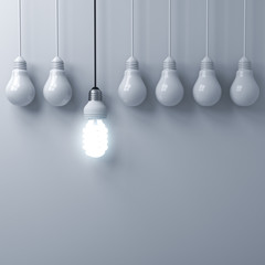 One hanging eco energy saving light bulb glowing and standing out from unlit incandescent bulbs on white wall background with shadow , leadership and different creative idea concepts . 3D rendering.