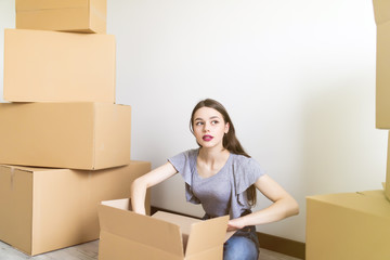 Woman packing and unpacking carton box when moving home. Relocation