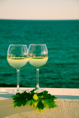 Two glasses with cold white wine served outside on terrace with green grape vine, luxury resort with sea view, romantic vacation