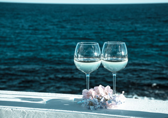 Two glasses with cold white wine served outside on terrace with pink tropical flowers, luxury resort with sea view, romantic vacation