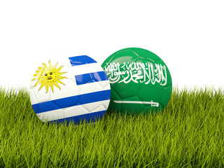 Uruguay vs Saudi Arabia. Soccer concept. Footballs with flags on green grass