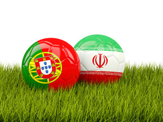 Portugal vs Iran. Soccer concept. Footballs with flags on green grass