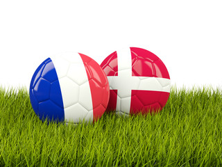 France vs Denmark. Soccer concept. Footballs with flags on green grass