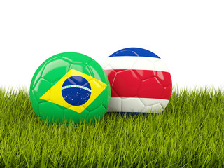 Brazil vs Costa Rica. Soccer concept. Footballs with flags on green grass