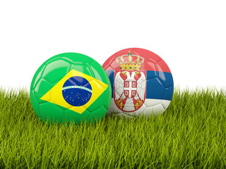 Brazil vs Serbia. Soccer concept. Footballs with flags on green grass