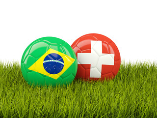 Brazil vs Switzerland. Soccer concept. Footballs with flags on green grass