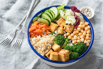 Nourishing buddha bowl with tofu, quinoa and vegetables. Healthy eating, healthy lifestyle, vegan food, vegetarian diet, modern lifestyle concept. Colorful buddha bowl on table. Selective focus