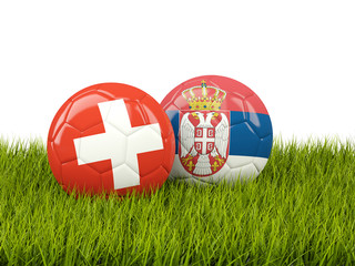 Switzerland vs Serbia. Soccer concept. Footballs with flags on green grass