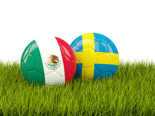 Mexico vs Sweden. Soccer concept. Footballs with flags on green grass