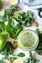 Smoothie detox with green fruits, vegetables, spinach and kale on white. Green smoothie and ingredients. Top view, selective focus