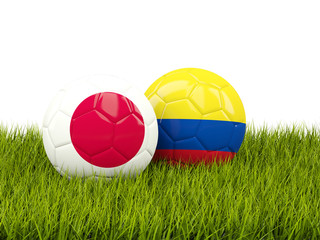 Japan vs Colombia. Soccer concept. Footballs with flags on green grass