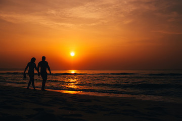 silhouettes of a couple walking along the beach by the sea at sunrise