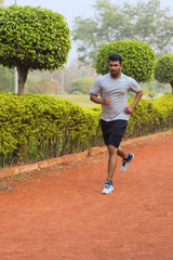 Young guy running on a jogging track