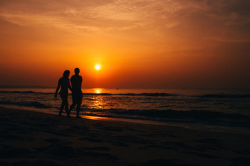 silhouettes of a couple in love on the beach by the sea on the background of orange sunrise