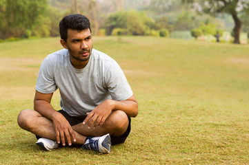 Young guy sitting and taking rest after morning exercise