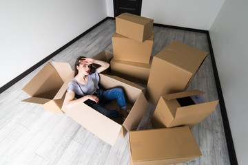 Young pretty tired woman sitting inside a box among a stack of moving boxes