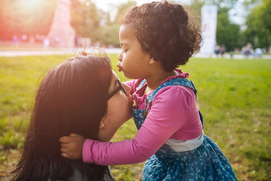 Cute curly mexican dark skinned toddler baby girl kissing her mother on forehead in european city square. Growing up, leadership, copying female psychology behavior concept.