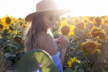 Young woman walking in the field with sunflowers.Beautiful young girl enjoying nature on the field of sunflowers at sunset.woman with long hair , back view. The concept of freedom.Sunflower background