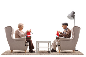Elderly woman and an elderly man seated in armchairs knitting