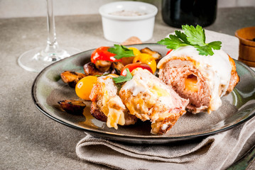 Homemade meat cutlet cordon bleu, grey stone background copy space