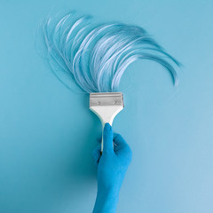Blue colored hand holding long hair brush