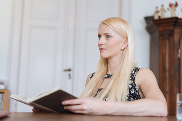 Young blond woman sitting reading a book