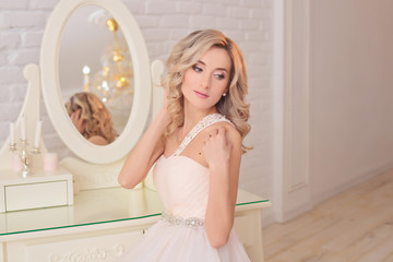 The bride gathers in the morning near the mirror. The bride is gathering in the morning. Stylish pink wedding dress. The bride with curly hair is spinning in a dress near the mirror.